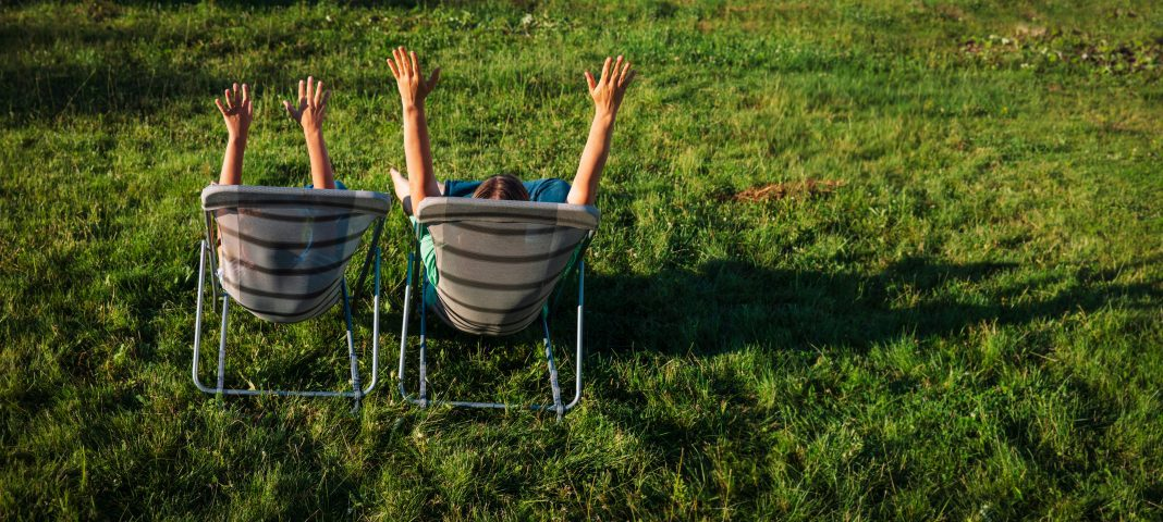 a photo from behind of a mom and her son sitting in chairs in the grass with their arms raised up in the air
