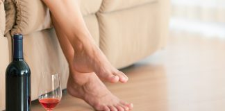 a woman sitting on a couch with a bottle of wine and a half empty glass by her feet