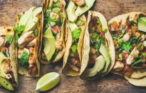 six soft tacos on a wooden tabletop with avocado and sliced limes