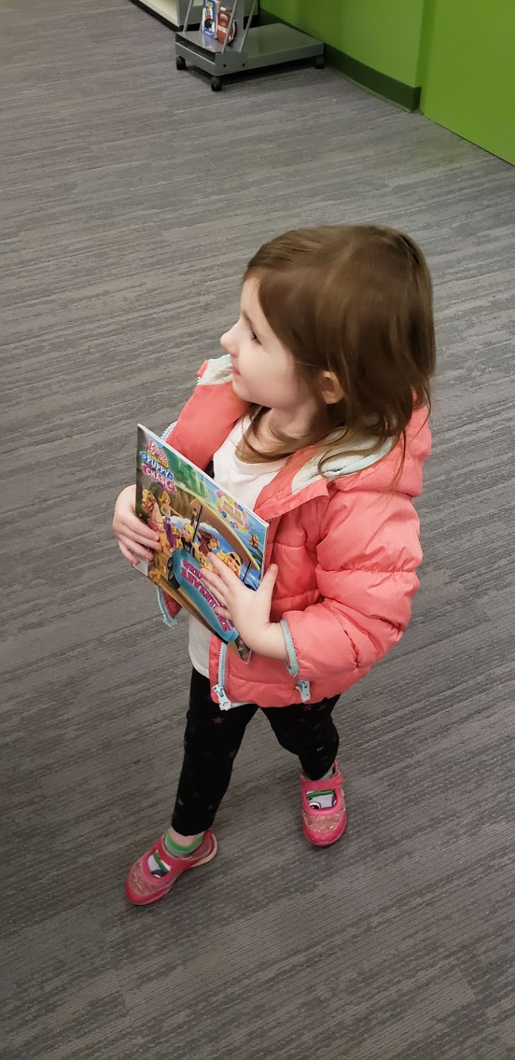 a little girl holding books at the library
