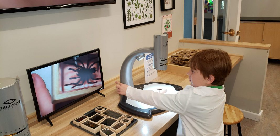a boy in a white lab coat using a microscope at The Magic House