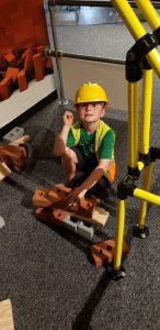 a boy in a construction hat playing with play bricks