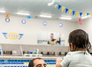 a dad reaching for his toddler daughter who is sitting on the edge of a pool, ready to get in and swim with him
