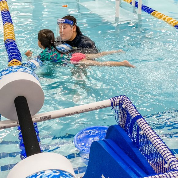 a girl in a bright colored swimsuit with a Foss Swim School swim instructor, learning about water safety in the pool