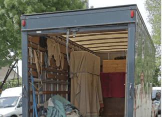a moving truck with it's back open, parked on a city street as an oak dresser sits on the ground in front of it, ready to be loaded