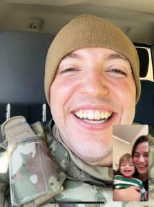 a video call with a man serving in the military smiling at his wife and son