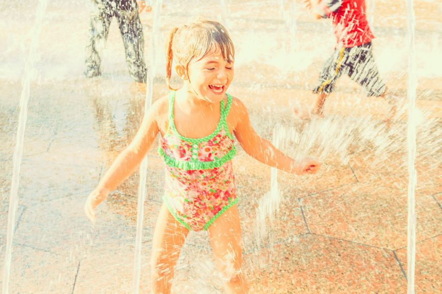 a young girl splaying at a splash pad