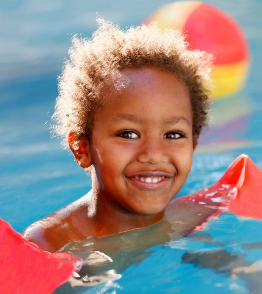 a young girl with floaties on her arms in the pool