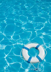 a white life preserver floating in a clear blue pool