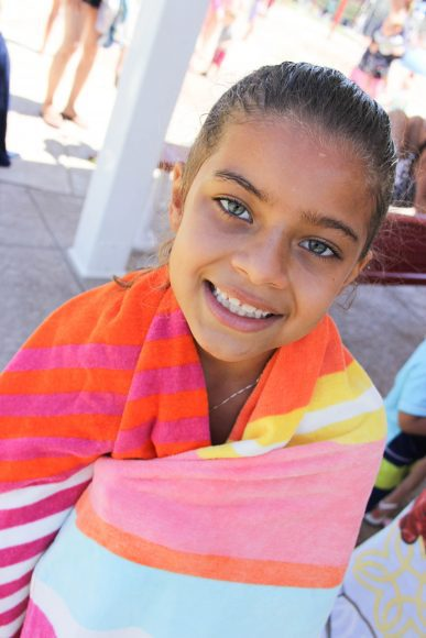 a girl wrapped up in a towel after swimming, smiling at the camera