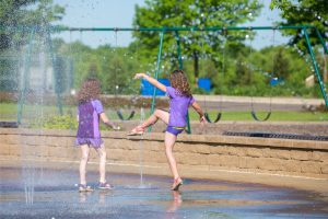 two girls dressed in purple as they play in the water feature at a park