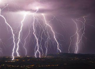lightning strikes across a gray sky