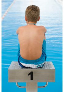 a photo of a boy from the back sitting on a diving platform