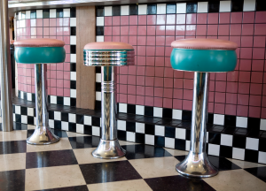 barstools at a soda fountain in bright pink and aqua set against black and white tile floor