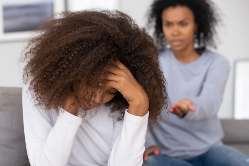 an upset tween with her head in her hands as her mom sits on the couch beside her