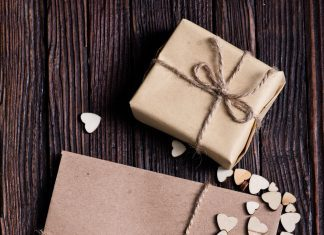 a letter sealed with wax on a table next to a small wrapped box and tiny hearts scattered around