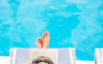 a woman in a lounge chair by the pool, reading a book