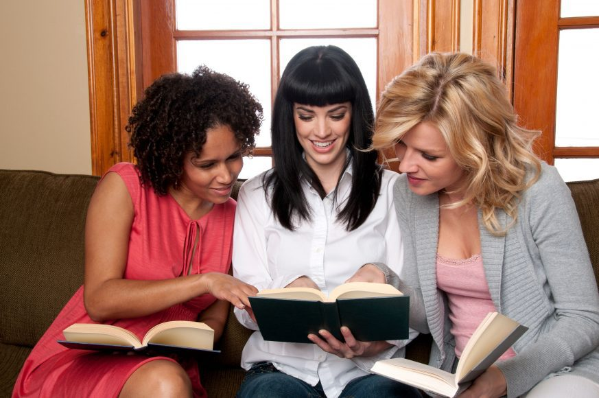 three women sitting on a couch, having a discussion about a book they're reading from their summer reading list
