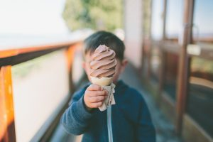 a boy holding a soft serve chocolate ice cream cone in front of his face as he stands outside on a porch
