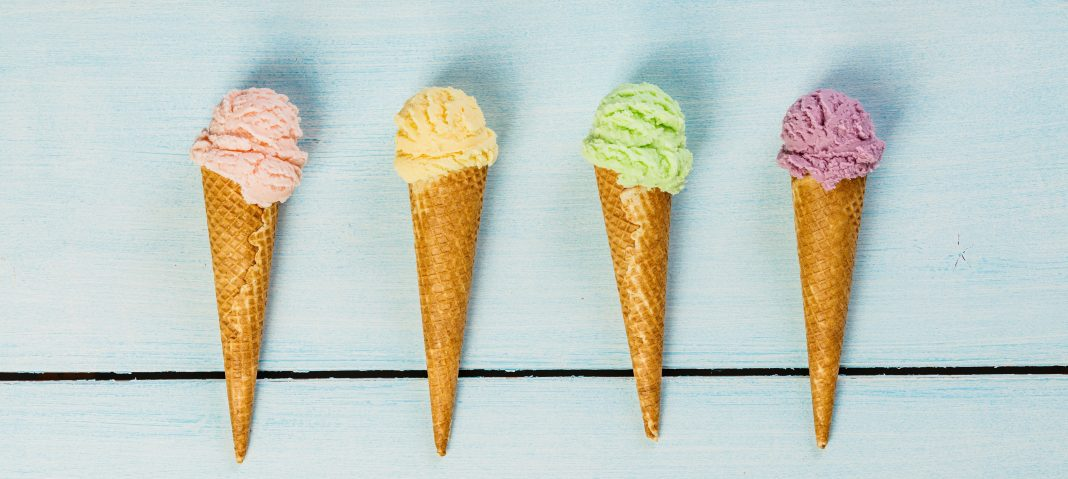 four ice cream cones with colorful scoops of ice cream on a light blue wooden table
