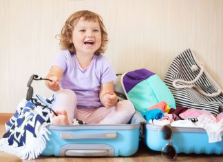 a little girl sitting inside of a suitcase as she packs up for a family vacation