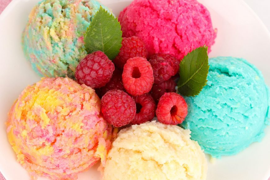 multicolored scoops of fruity ice cream with fresh raspberries in the middle