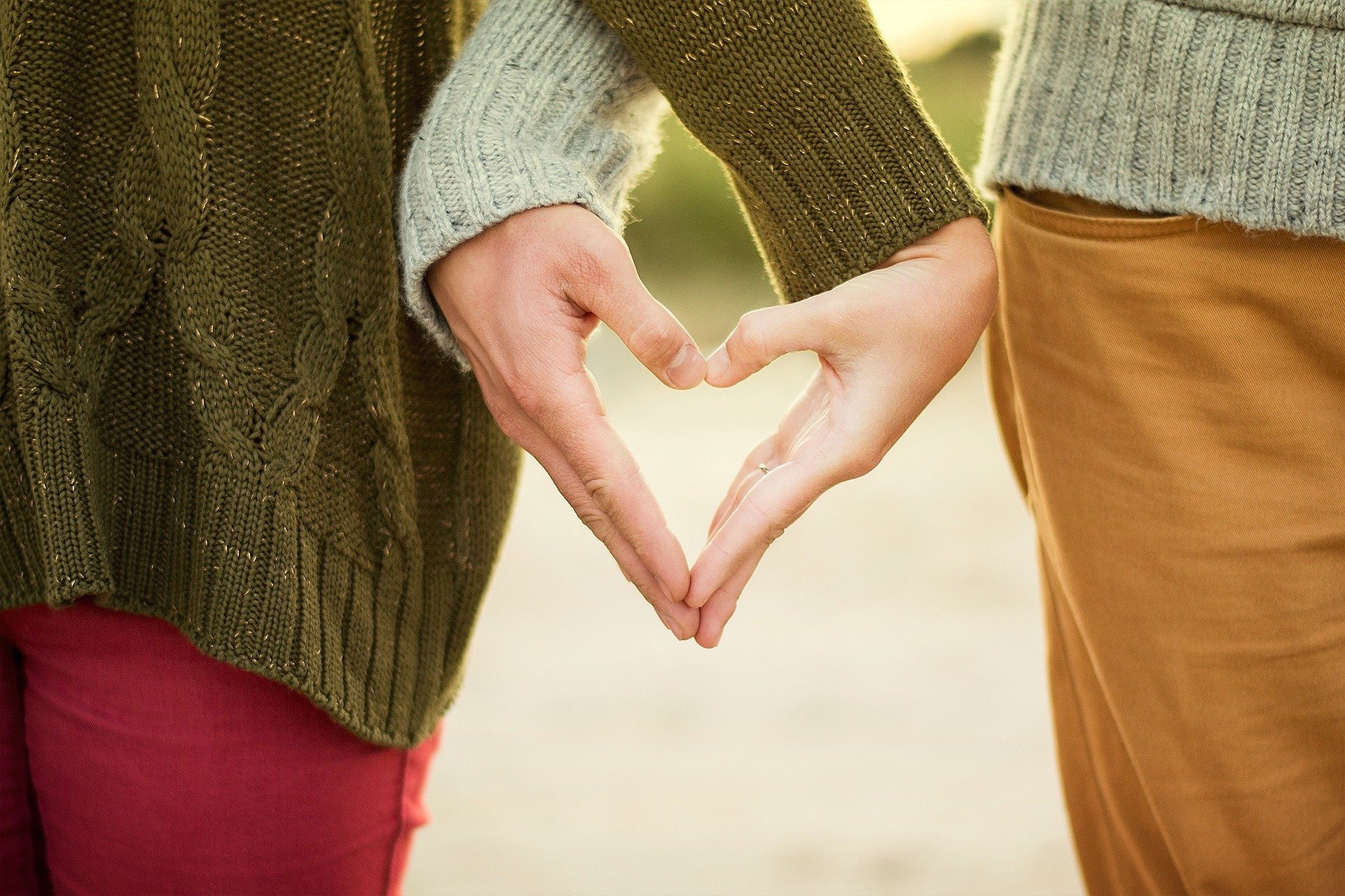 a close up of a couple holding their hands together in the shape of a heart, to represent love as their family motto