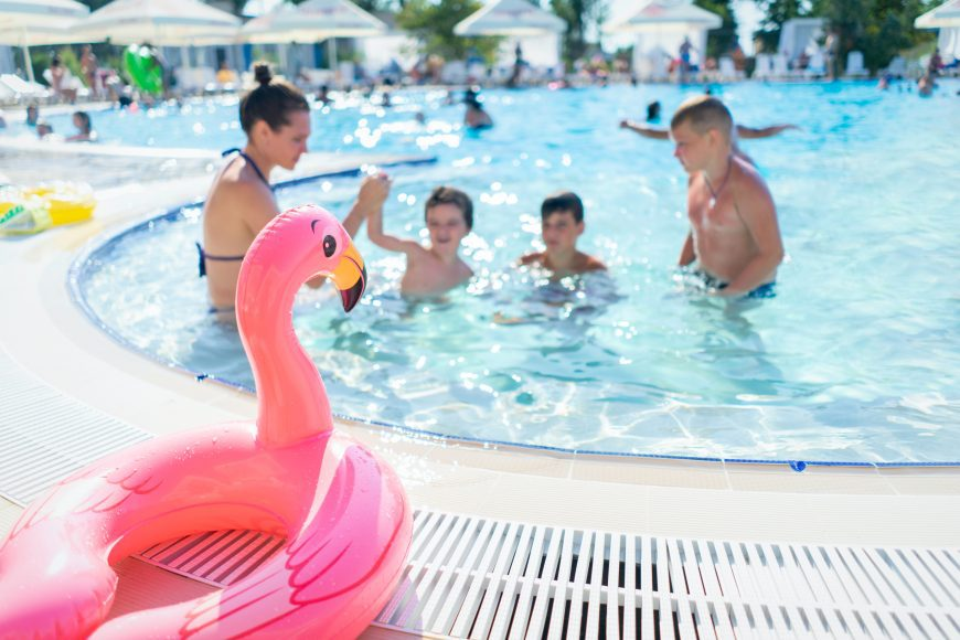 kids swimming at a neighborhood pool with a flamingo floatie on the side of the pool