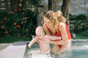 a mom holding her baby in the pool
