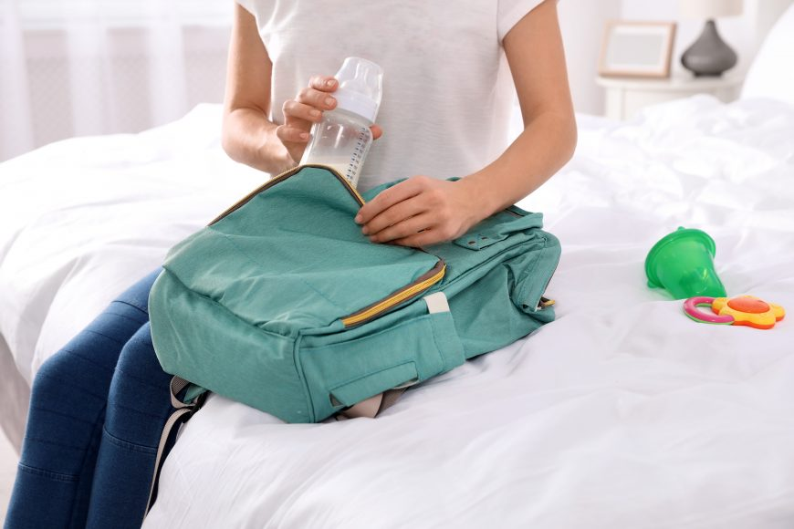 a woman sitting on a bed with a white comforter as she packs a bottle of breastmilk in her baby's backpack for daycare