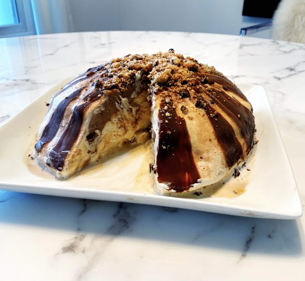 A layered ice cream bombe on a white platter on a marble countertop
