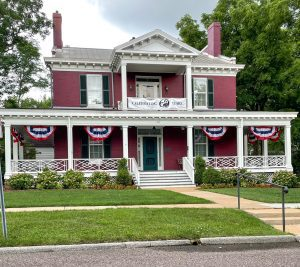 a red house with a white wraparound porch part of the Kirkwood Historical Society