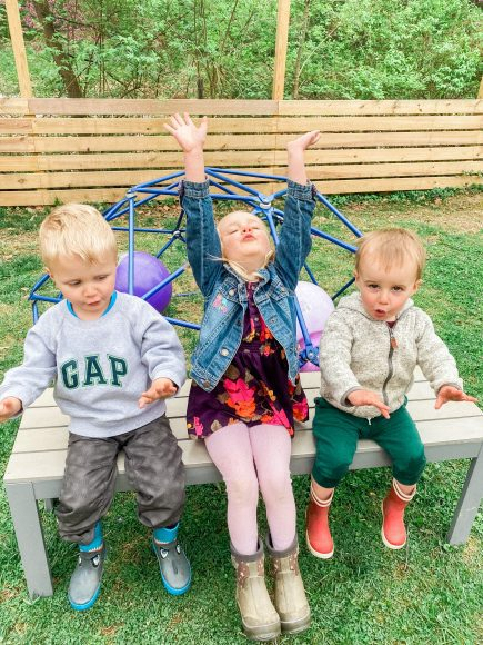 three little kids sitting on a bench outside in front of a climbing structure
