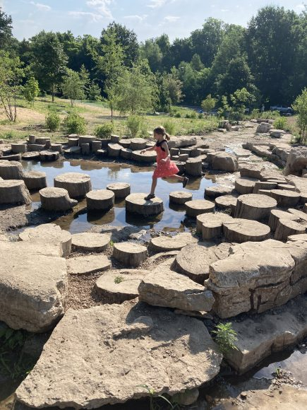 a girl jumping from stump to stump across a stream at Forest Park and the Nature Playscape feature