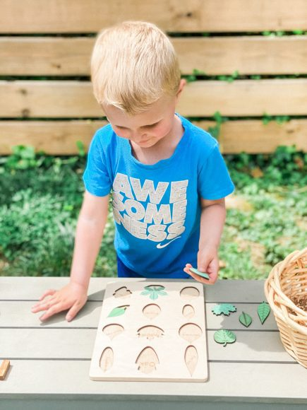 a toddler putting a puzzle together on a table outdoors, enjoying nature