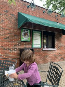 a toddler girl enjoying a snack outside The Snack Shack in Overland Park, Kansas