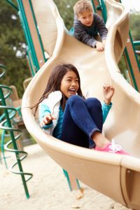 a young girl sliding down a curvy slide at a park