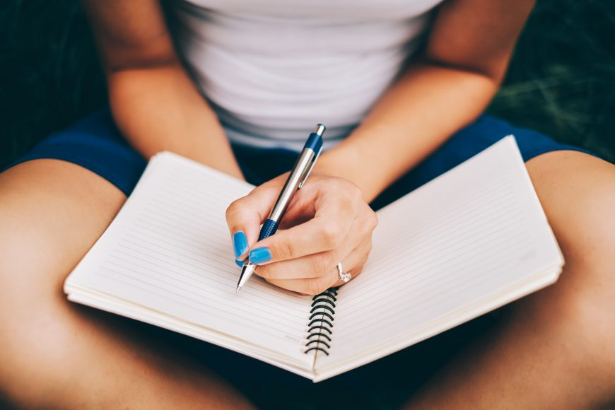 a close up of a woman, with blue nail polish, holding a pen as she is journaling in a notebook