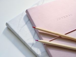 two journals with colored pencils laying across the top