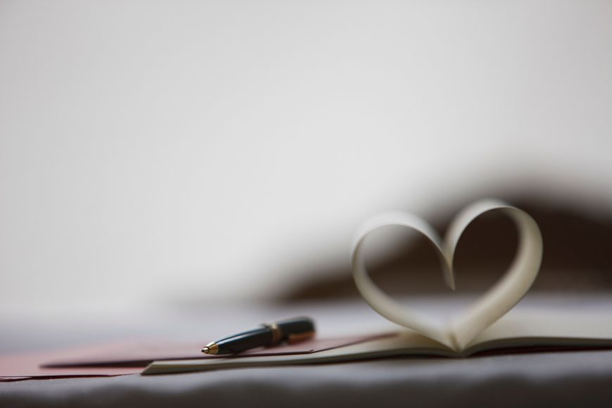 a pen on top of a journal that has two pages folded into the shape of a heart