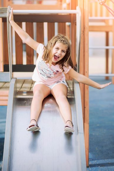 a girl smiling with her arms out as she slides down a metal slide