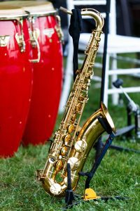 a trumpet leaning against a chair in the grass representing the outdoor summer concerts in O'Fallon