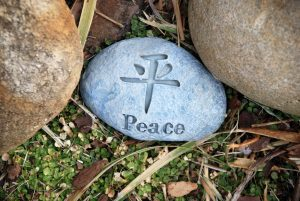 """a stone in the grass with the word """"Peace"""" in English and Chinese"""