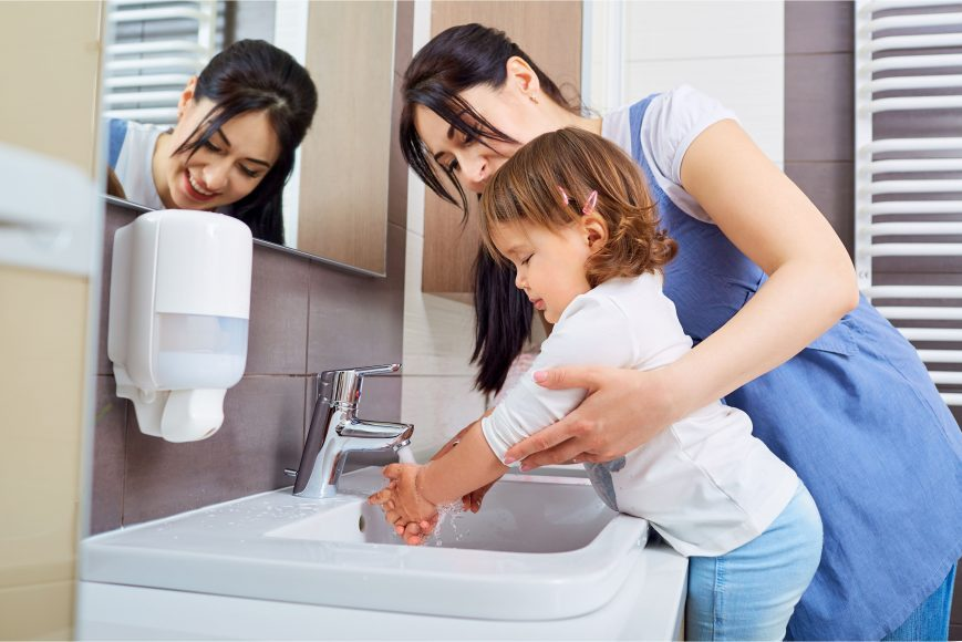 a mom helping her child wash hands to keep germs away