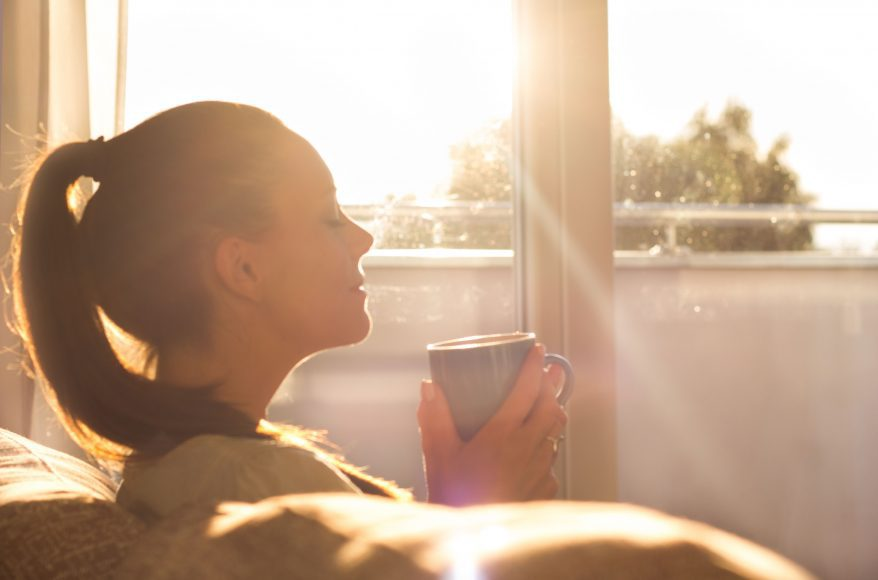 a woman sitting on a couch as the sun rises through the window, drinking coffee