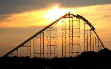 roller coaster cars at the crest of a hill, starting the descent down as the sun sets in the background