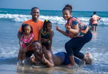 an African American family, posing in the waves on the beach as the mom gives a peace sign