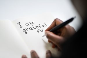 """a journal with the words, """"I am grateful for ..."""" written a the top of the page"""