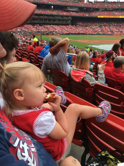 a toddler girl sitting on her dad's lap as they watch Cardinals baseball