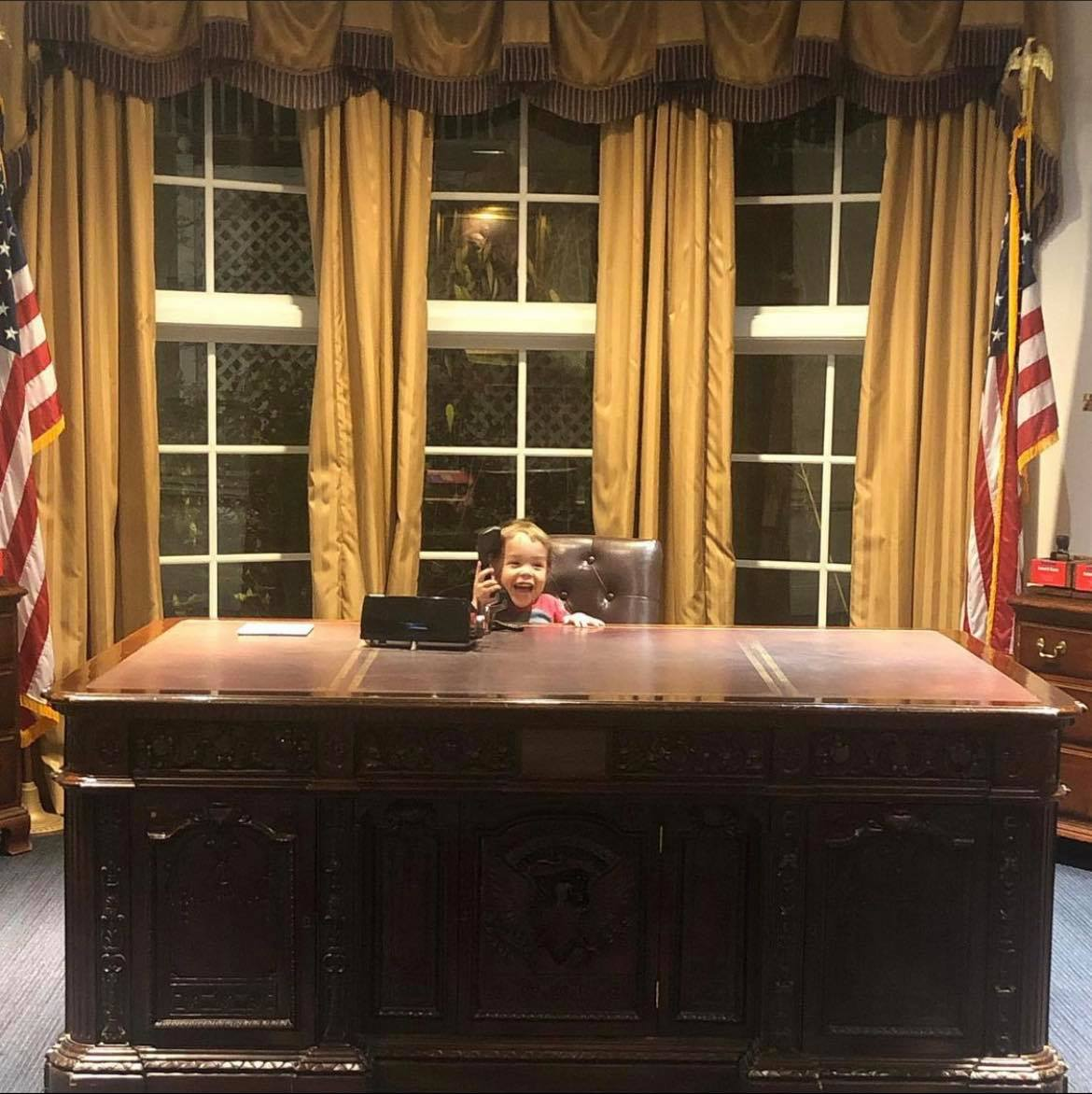 a child sitting at a desk in a replica of the Oval Office at the Magic House in Kirkwood, MO